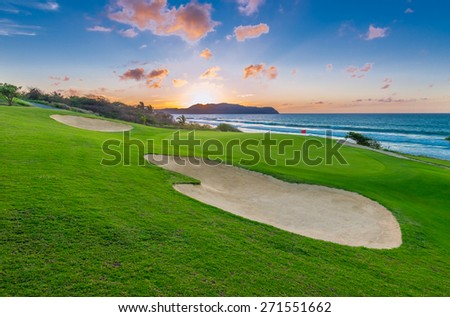 Sand bunkers and a red flag at the beautiful golf course at the ocean side at sunset, sunrise time. - stock photo