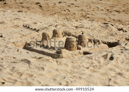 sand castle building by child - stock photo