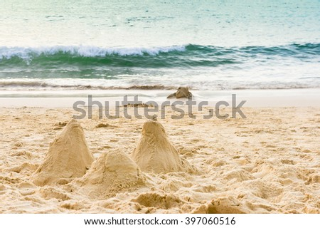 Sand castle on summer paradise beach. Sand castle on wavy summer sea. Summer paradise beach, Karon, Phuket. Summer background at Karon beach, Phuket, Thailand. Sand beach castle as summer background. - stock photo
