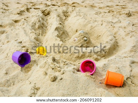 Sand castle on the beach four colorful molds. Vacation concept. - stock photo