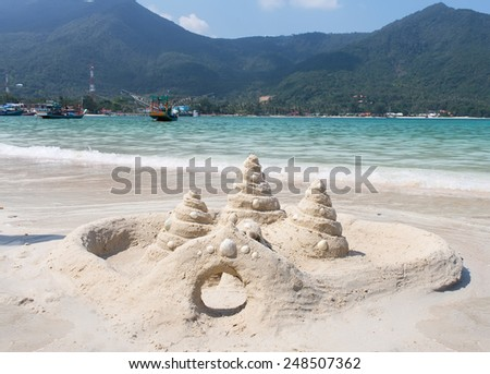 sand castle on the beach Koh Phangan with sail boats on backgroud - stock photo