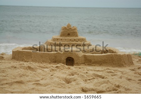 Sand castle  the beach with the ocean in the background - stock photo
