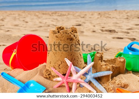 sand castle with starfish  on  sunny summer beach  - stock photo