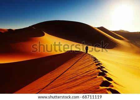 Sand dune climbing at sunrise, Sahara Desert, Algeria - stock photo