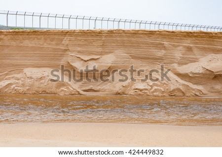 Sand dune collapse down to a small canal revealed texture inside - stock photo