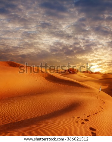 Sand dunes field at sunset and traces of a little girl walking along the desert - stock photo
