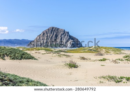 Sand dunes & majestic Morro Rock over looking the Pacific Ocean, next to Morro Strand state beach, on the California Central Coast, near Cambria, CA. - stock photo