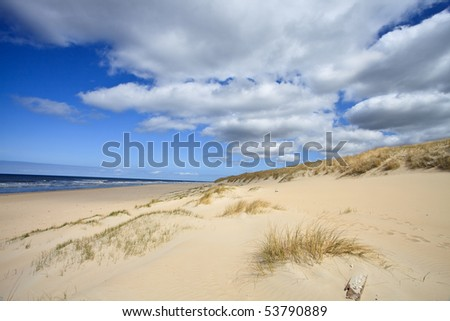 Sand dunes near to the sea with cloudy sky - stock photo
