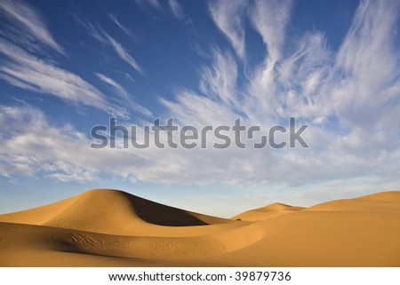 sand dunes with cloudy blue desert sky in the moroccan sahara - stock photo