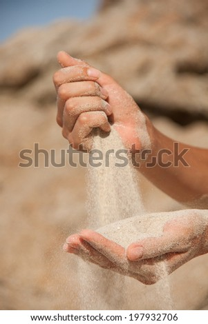 sand flows through the female fingers
