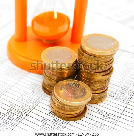 Sand-glass and gold a coin. On documents. - stock photo