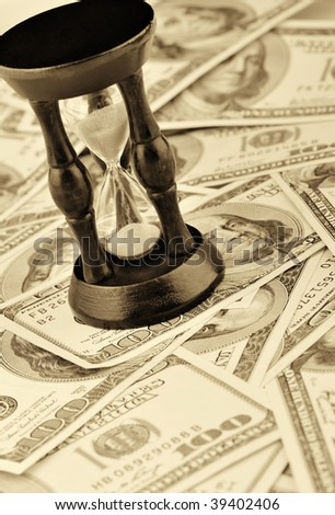 Sand-glass on dollars blue tone. Concept time - money - stock photo
