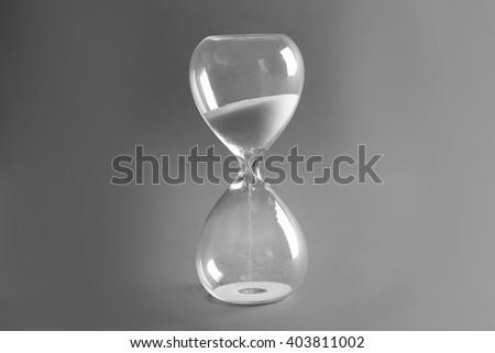 Sand hourglass on grey background - stock photo