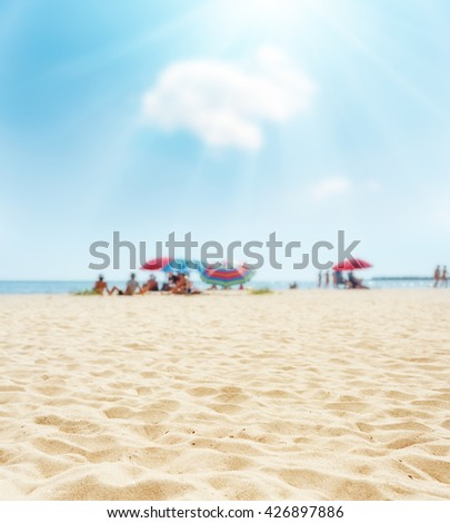 sand on beach closeup and sun in blue  sky. soft focus on bottom of picture - stock photo