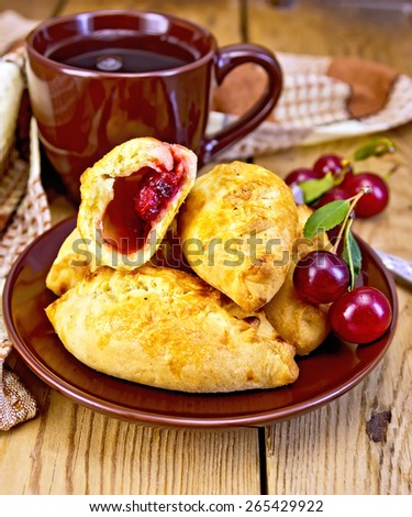 Sand patty with cherries on a brown plate, cup, napkin, on a wooden boards background - stock photo