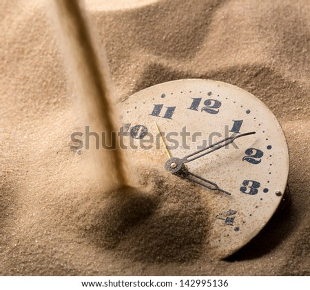 Sand pouring on old clock face - stock photo
