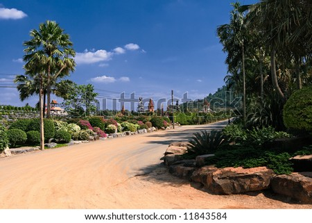 Sand road in palm and flower garden, Thailand in sunny summer day - stock photo