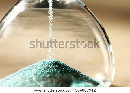 Sand running through the bulbs of an hourglass measuring the passing time in a countdown to a deadline, on a dark background with copy space. - stock photo