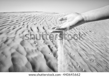 Sand slipping through the fingers of a woman's hand in the desert of Sahara in Tunisia. - stock photo