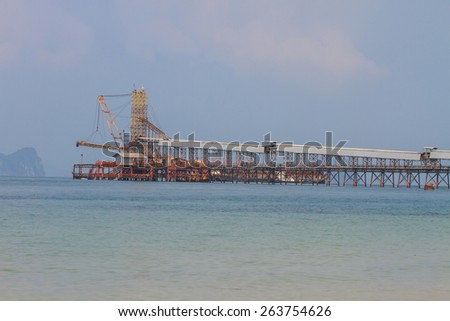 Sand sucking ship working in the sea - stock photo