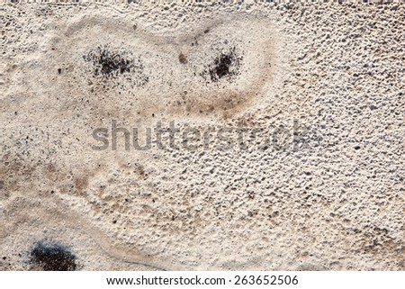 Sand surface after the rain with the visible traces of the raindrops and grains of black soil - stock photo