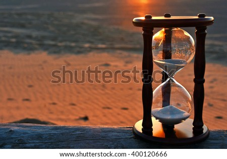 sand timer on weather log on the beach with sunset glow - stock photo