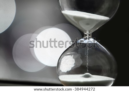Sand Timer with white sand. With beautiful bokeh background.  - stock photo