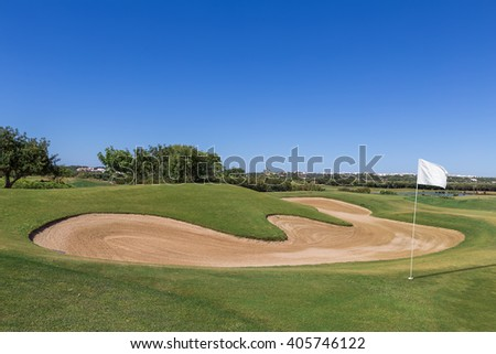 Sand trap on the golf course with a white flag.
