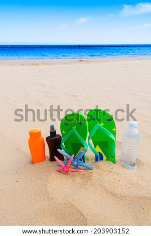 sandals and  bottle of water and suntan creams on sandy beach by sea side - stock photo