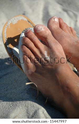 Sandals and feet in sand