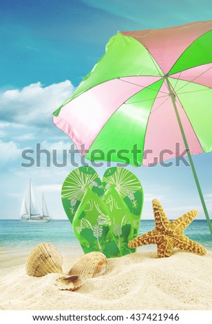 Sandals and seashells with beach umbrella at the ocean - stock photo