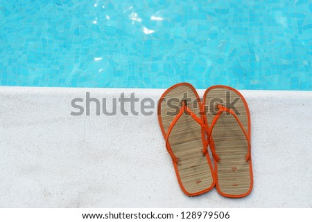 Sandals at the pool on a very sunny day - stock photo