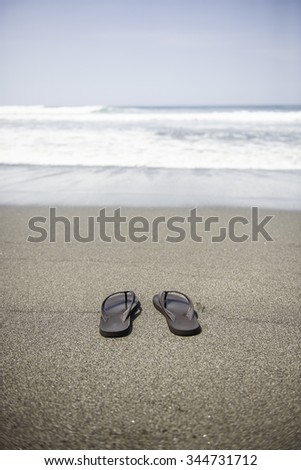 Sandals on the beach, ocean in the background - stock photo