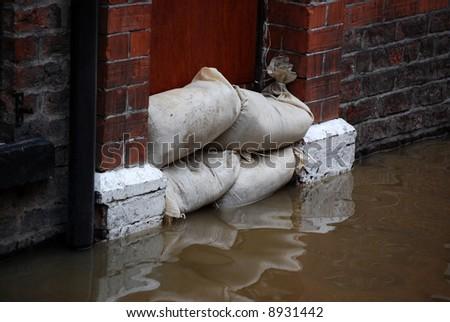 Sandbag barrier in doorway of flooded street in York. - stock photo