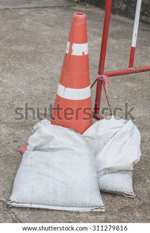 Sandbags placed near a traffic cone, to warning and prepare flood protection. - stock photo