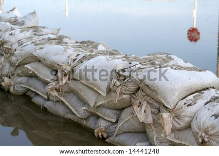 Sandbags stop flood waters.  In the reflection is a Stop sign.