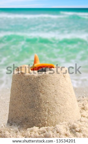 Sandcastle and shells next to pretty ocean - stock photo