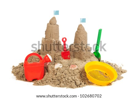 sandcastle at the beach with plastic toys isolated over white background - stock photo