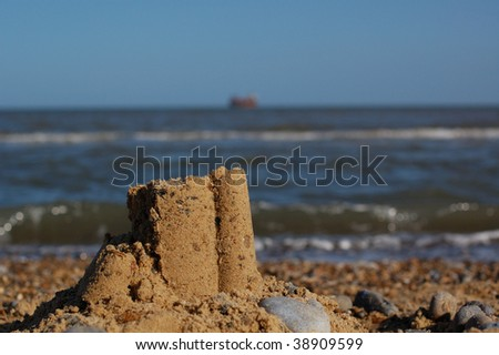 Sandcastle on beach with sea in the background - stock photo