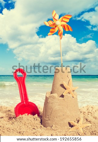 Sandcastle on the beach with pinwheel and starfish - vintage filter effect - stock photo