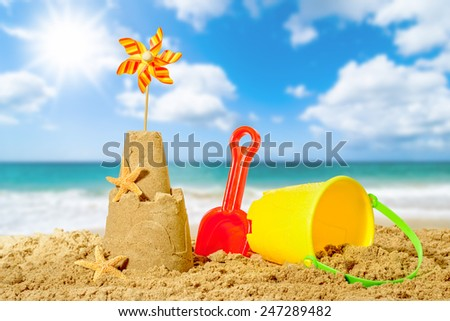 Sandcastle with bucket and spade with beach blur background - stock photo