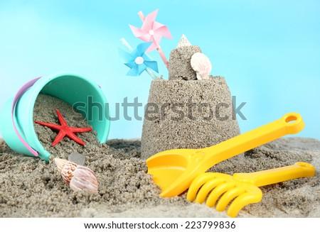 Sandcastle with pinwheel on sandy beach  - stock photo