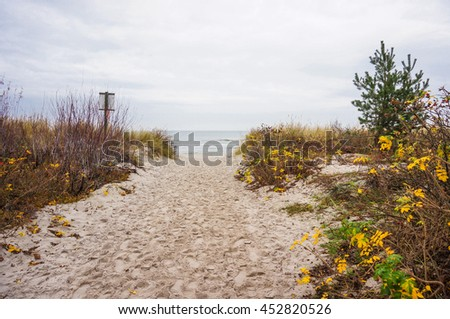 Sandpath leading to a beach on a cloudy day - stock photo