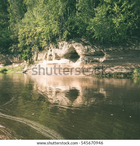 sandstone cliffs on the river shore in the Gaujas National Park, Latvia - instant vintage square photo