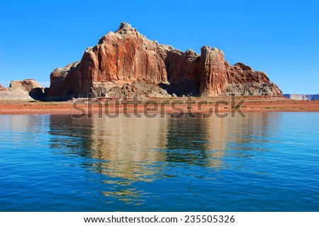 Sandstone monolith is reflected in the calm waters of Lake Powell in Utah.  Blue sky and red sandstone gives color to the landscape. - stock photo