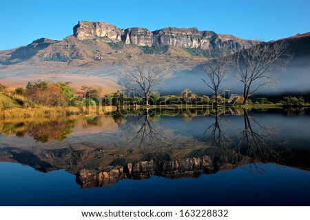 Sandstone mountains with symmetrical reflection in water, Royal Natal National Park, South Africa  - stock photo
