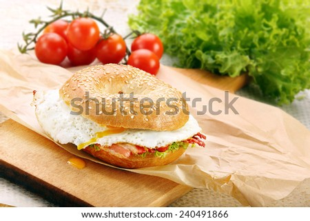 Sandwich bagel with fried bacon and egg on chopping board - stock photo