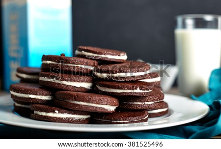 Sandwich chocolate or cacao cookies filled with butter cream on wood background with milk on back. - stock photo