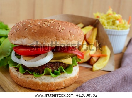Sandwich home hamburger soft buns, cheese, tomatoes and juicy burgers. Cabbage salad. French fries. Fast food. - stock photo