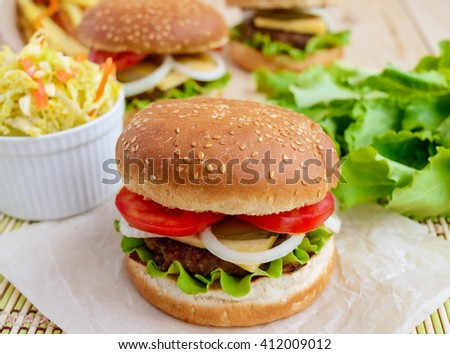 Sandwich home of the hamburger buns soft, juicy burger, cheese, tomato, parsley. Salad savoy cabbage. Fast food. - stock photo
